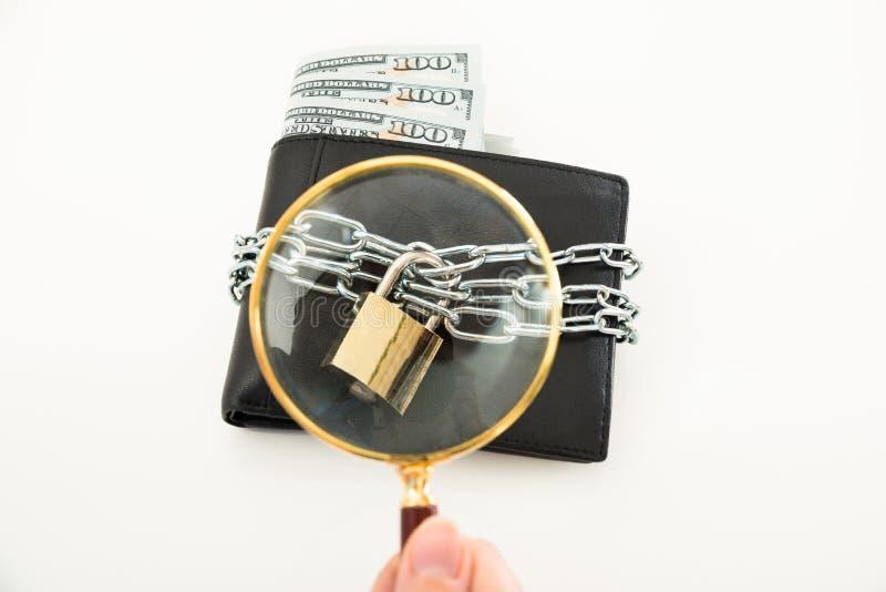Personhand med förstoringsglaset över plånboken arkivfoto