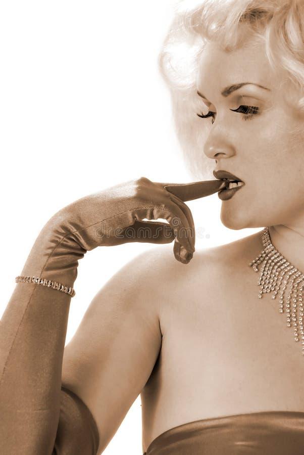 Personificador atractivo de Marilyn que muerde en el dedo con guantes imagen de archivo libre de regalías