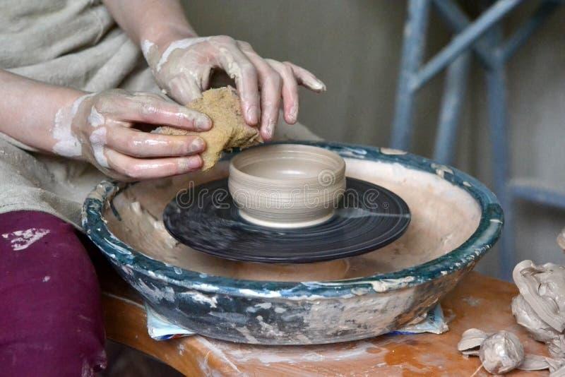 personkeramikern gör leratillbringaren på en keramiker` s att rulla arkivbilder