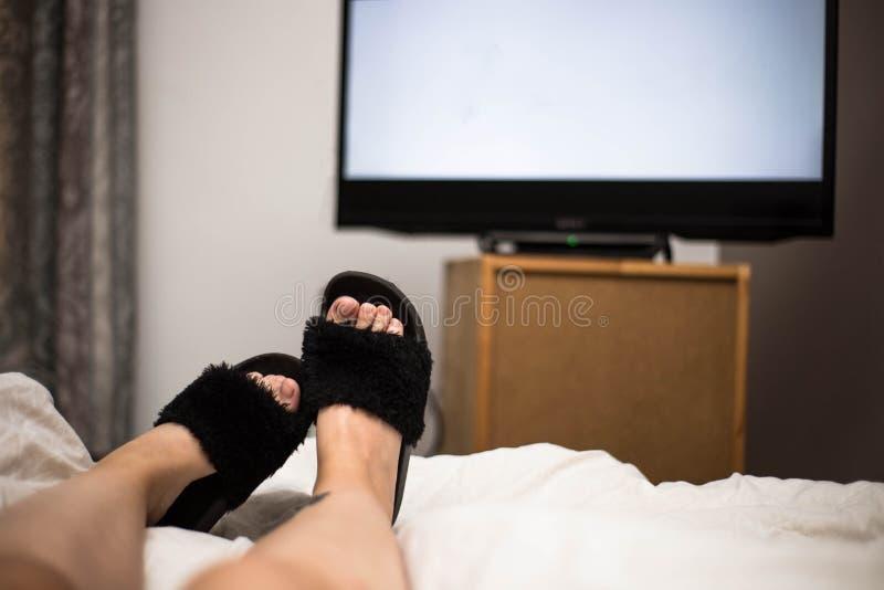 PersonklockaTV på natten i hans säng med hans fot som bär svarta Flip Flops TVskärmen är tom vit royaltyfri fotografi