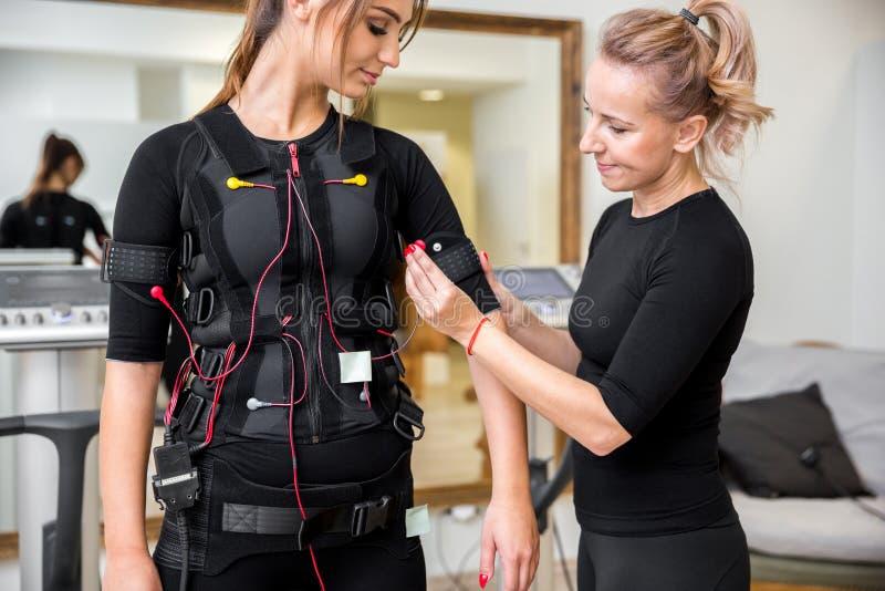 Personlig instruktör som förlägger ems-dioder på ung kvinna royaltyfria bilder