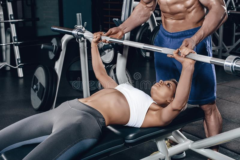 Personlig instruktör som hjälper en ung kvinna att lyfta en skivstång, medan utarbeta i en idrottshall arkivbild
