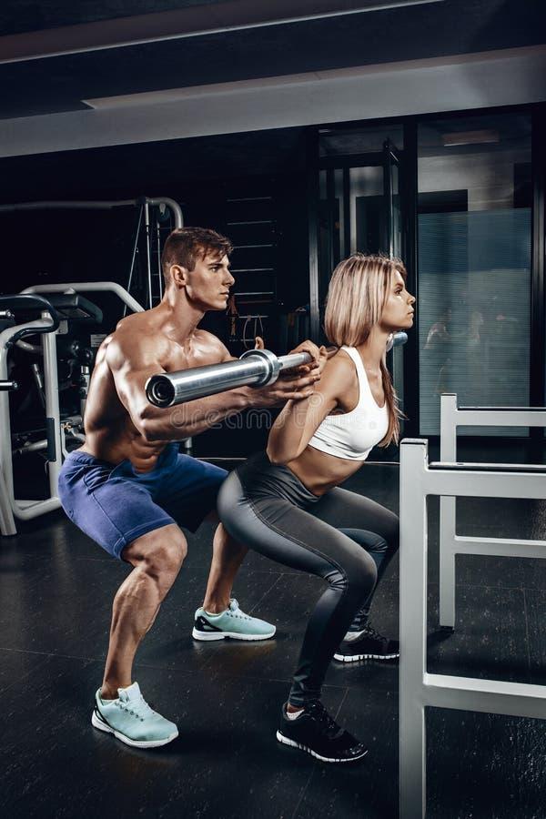Personlig instruktör som hjälper en ung kvinna att lyfta en skivstång, medan utarbeta i en idrottshall royaltyfria bilder