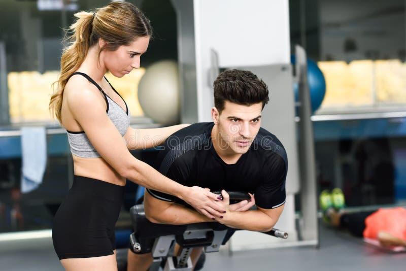Personlig instruktör som hjälper en ung man att lyfta vikter arkivbild