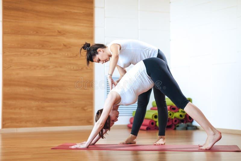 Personlig instruktör som hjälper gravida kvinnan, medan göra yoga royaltyfria foton