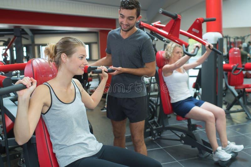 Personlig instruktör som hjälper klienten på bröstkorgmaskinen i idrottshall arkivbilder