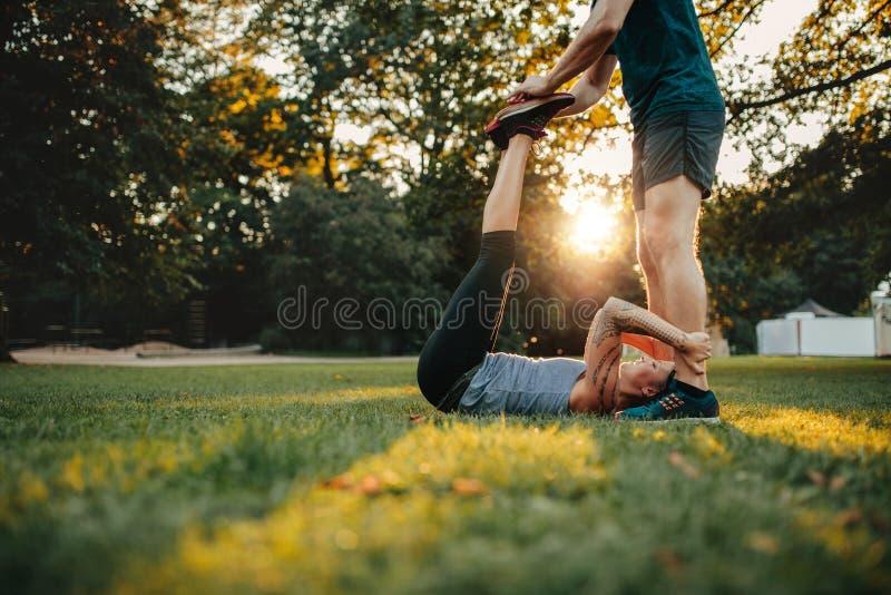 Personlig instruktör som hjälper kvinnan i benet som sträcker genomkörare fotografering för bildbyråer