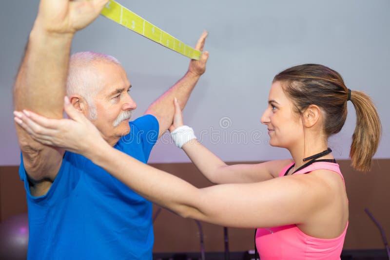 Personlig-instruktör som utarbetar med utbildning för man för elastisk musikband royaltyfri foto