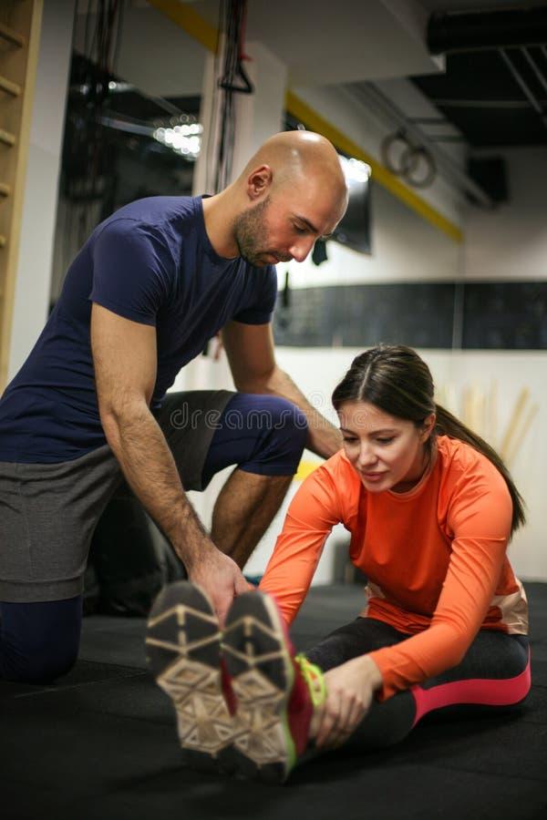 Personlig instruktör som utbildar hans klient i idrottshallen royaltyfri bild