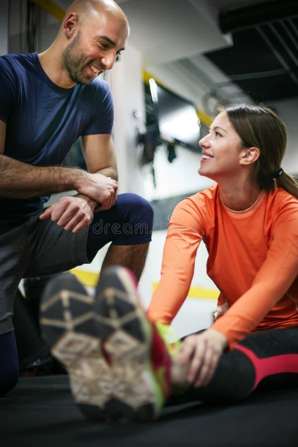 Personlig instruktör som utbildar hans klient i idrottshallen arkivbild