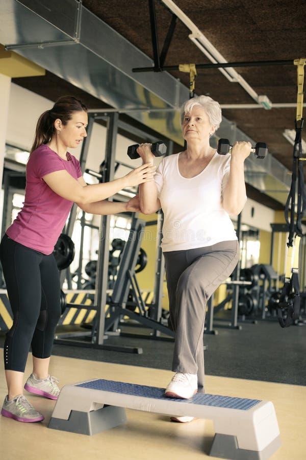 Personlig instruktörarbeteövning med den höga kvinnan i idrottshallen royaltyfri bild