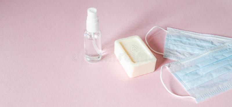 Personlig skyddsutrustning mot olika virus - medicinska masker, flasksaftmedel och tvål på rosa bakgrund royaltyfri fotografi