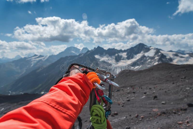 Personlig syn på en hand med klätterutrustning hög i bergen Bergsbestigning royaltyfri foto
