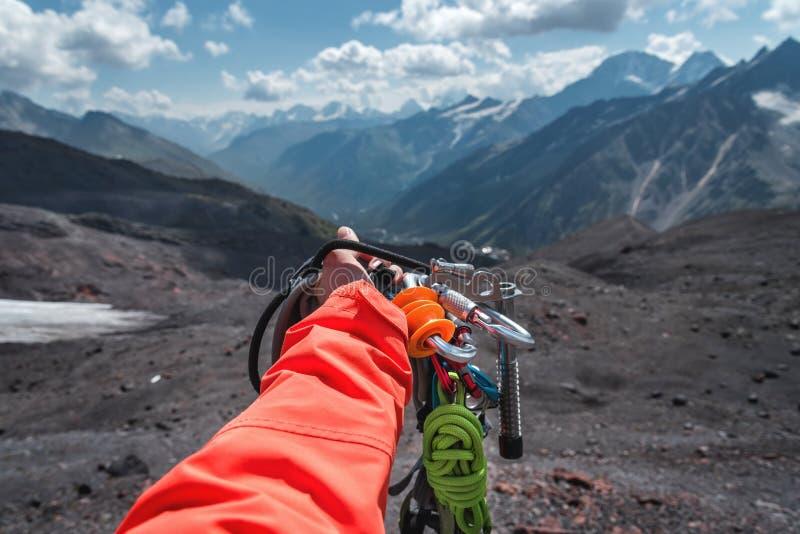 Personlig syn på en hand med klätterutrustning hög i bergen Bergsbestigning royaltyfria bilder