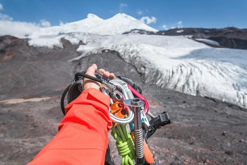 Personlig syn på en hand med klätterutrustning hög i bergen Bergsbestigning royaltyfri bild