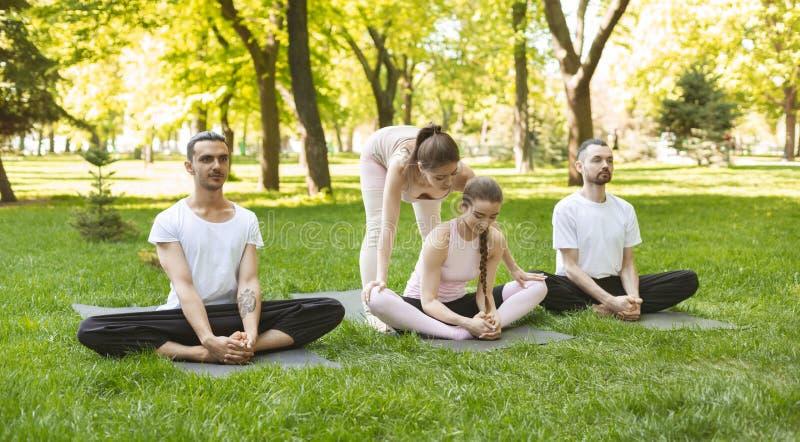 Personlig yogainstruktör som hjälper att förbättra böjlighet till hennes student royaltyfri bild