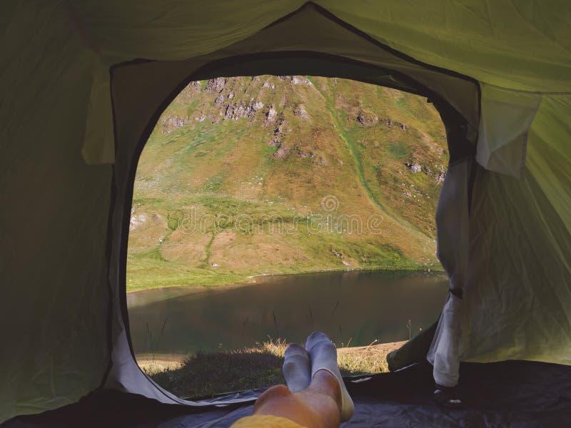 Personligt perspektiv av camparen i tält i de schweiziska fjällängarna royaltyfria bilder