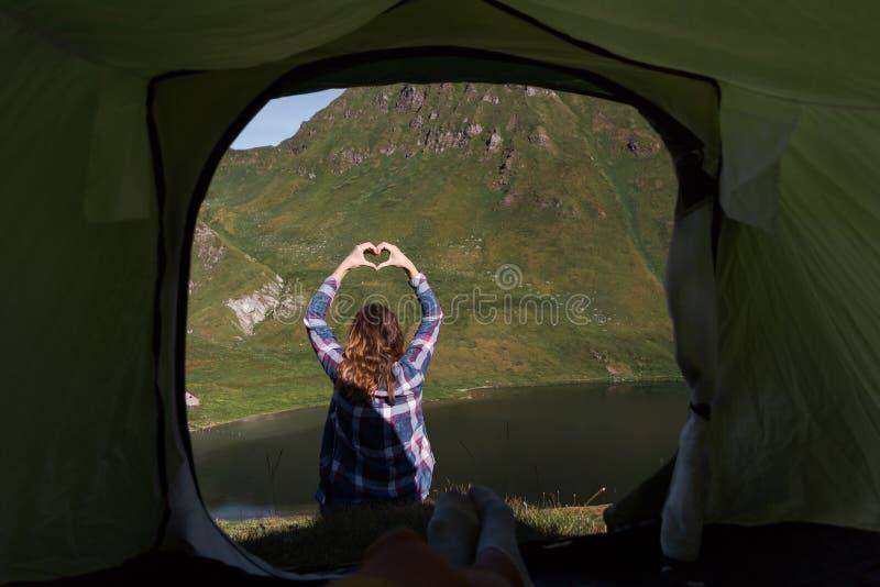 Personligt perspektiv av en manlig campare i tält i de schweiziska fjällängarna med en ung kvinna som gör handhjärtaform som är f royaltyfri fotografi