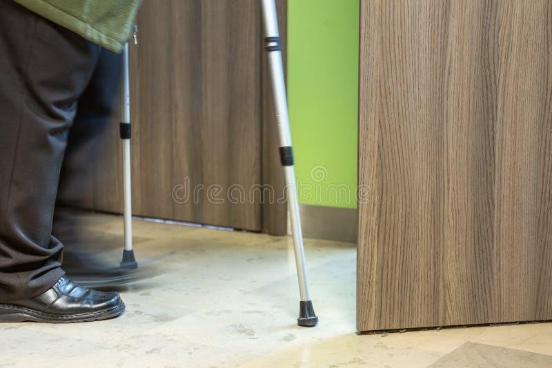 Personne âgée à l'aide des béquilles entrant dans la porte ouverte pour voir un doct photos stock