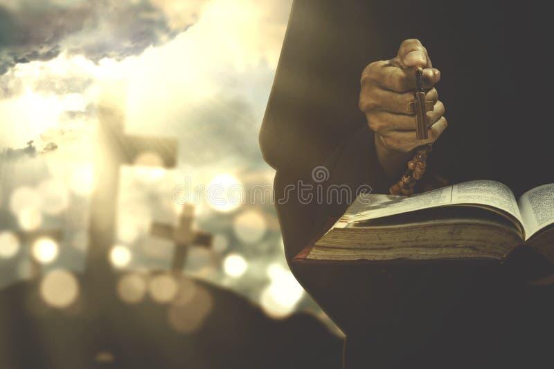 Personne adorant avec la bible et le chapelet photographie stock libre de droits