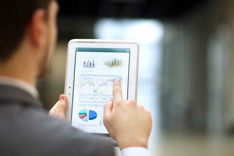 personne analysant des statistiques financières affichées sur l'écran de comprimé photos libres de droits
