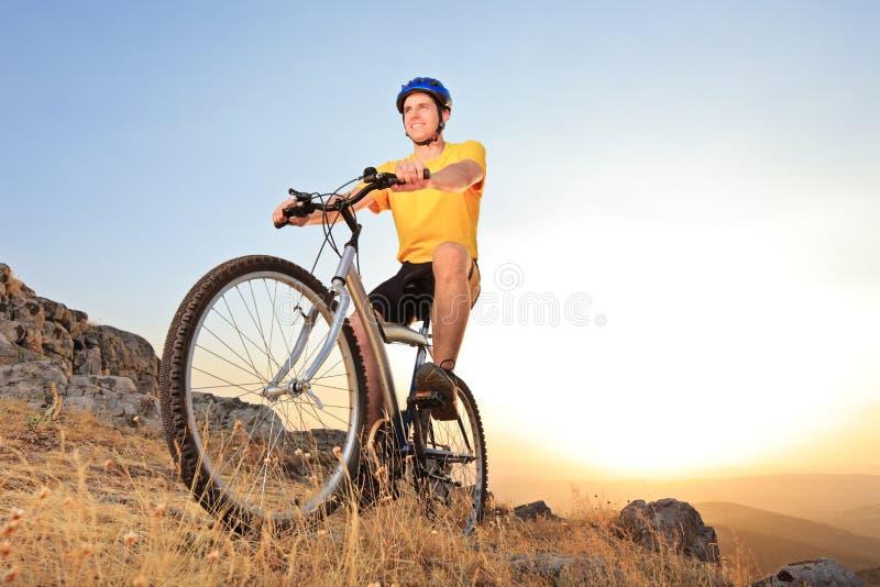 Personne conduisant un vélo de montagne sur un coucher du soleil photo stock