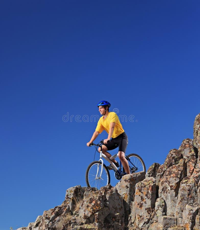 Personne conduisant un vélo sur des roches contre le ciel bleu photos libres de droits