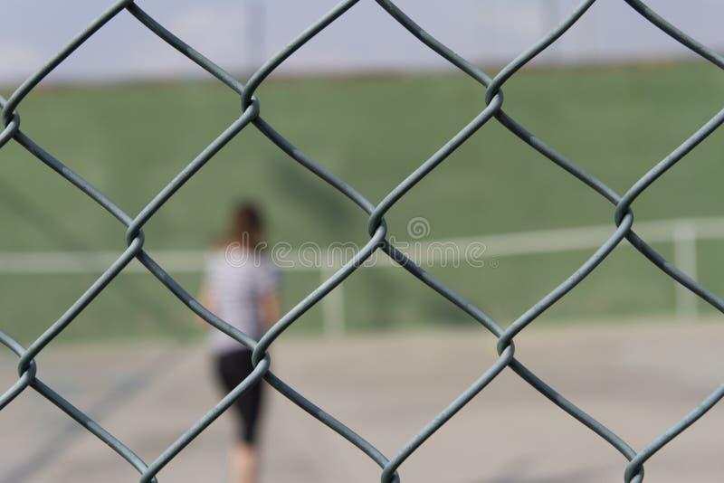 Personne derrière une barrière en métal photos stock