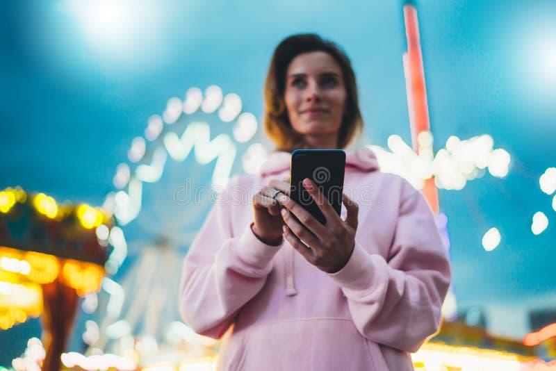 Personne dirigeant le doigt sur le smartphone d'écran sur la lumière de bokeh de fond de defocus dans la rue de soirée, fille de  photo libre de droits