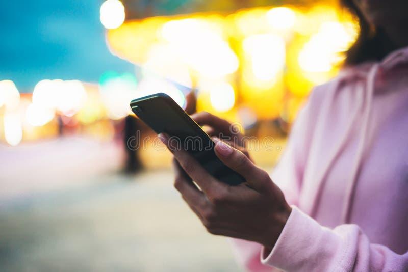 Personne dirigeant le doigt sur le smartphone d'écran sur la lumière de bokeh de fond de defocus dans la rue de soirée, fille de  photo stock