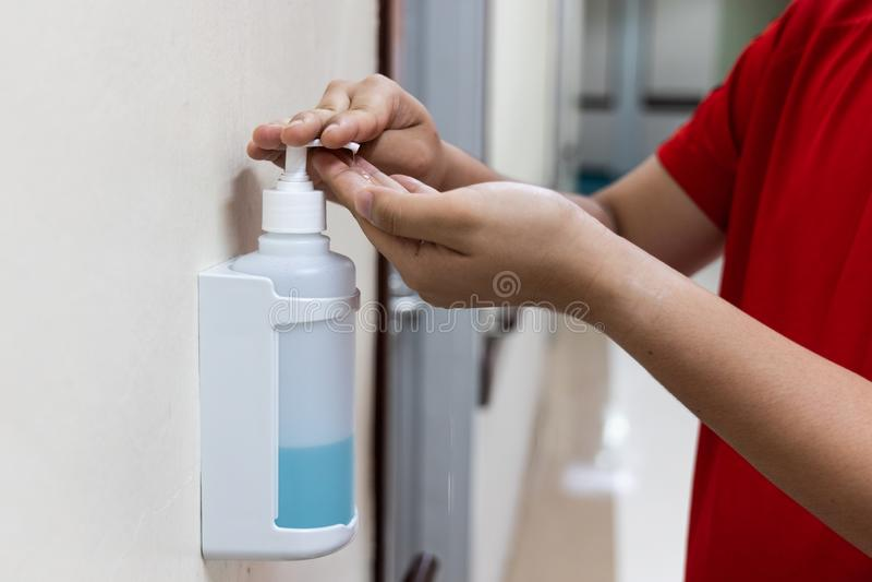 Personne distribuant le liquide désinfectant d'aseptisant sur la main dans les hos images stock