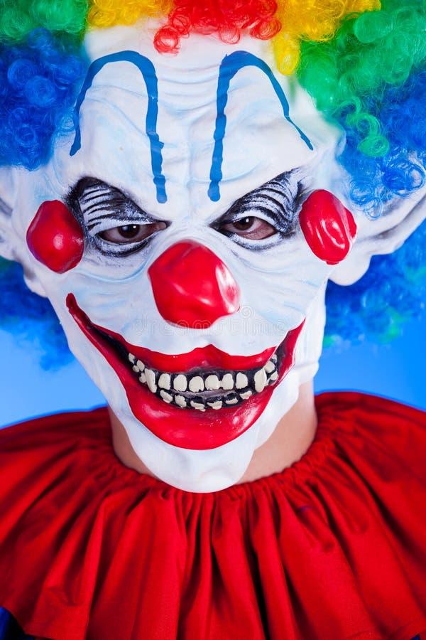 Personne effrayante de clown dans le masque de clown sur le fond bleu images libres de droits