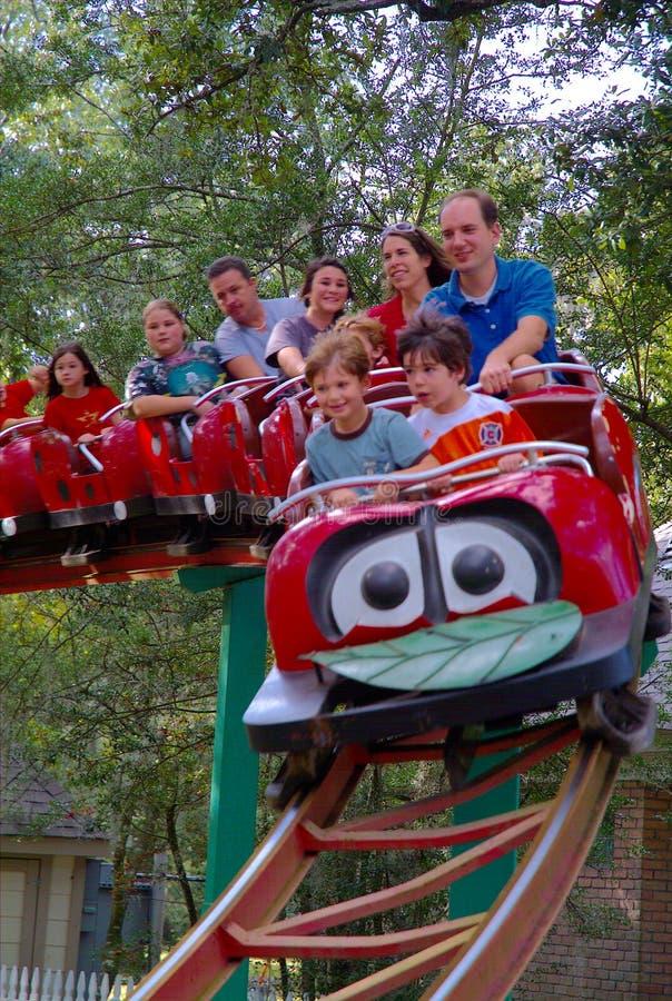 Personne-enfants et adultes sur des montagnes russes de parc d'attractions images libres de droits
