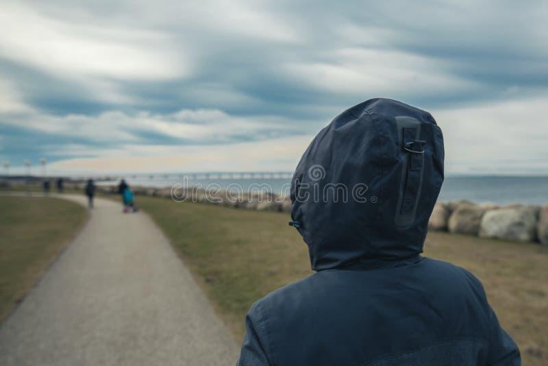Personne féminine à capuchon seule par derrière la position au bord de la mer photo stock