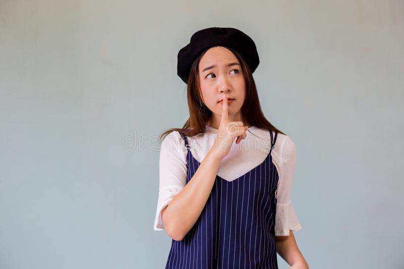 Personne féminine asiatique avec le doigt dans la bouche Le portrait de plan rapproché de la jeune femme montre chut un signe de  photo libre de droits