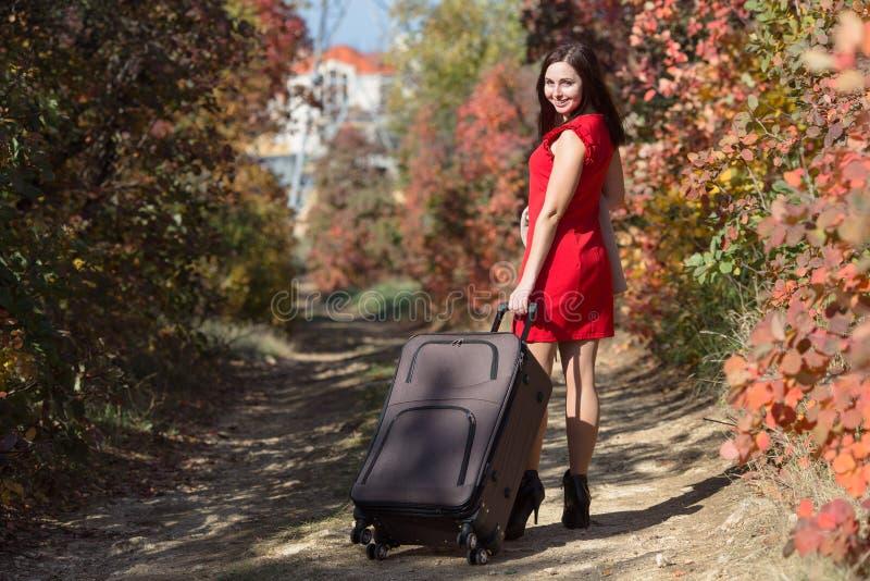 Personne féminine dans la robe rouge marchant sous des arbres d'automne image libre de droits