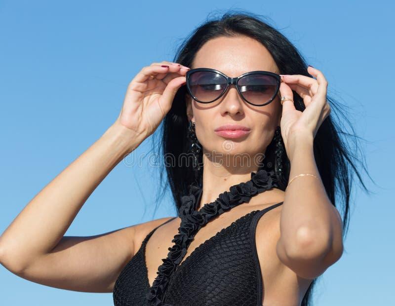Personne féminine dans le maillot de bain en un seul morceau ajustant des lunettes de soleil image stock
