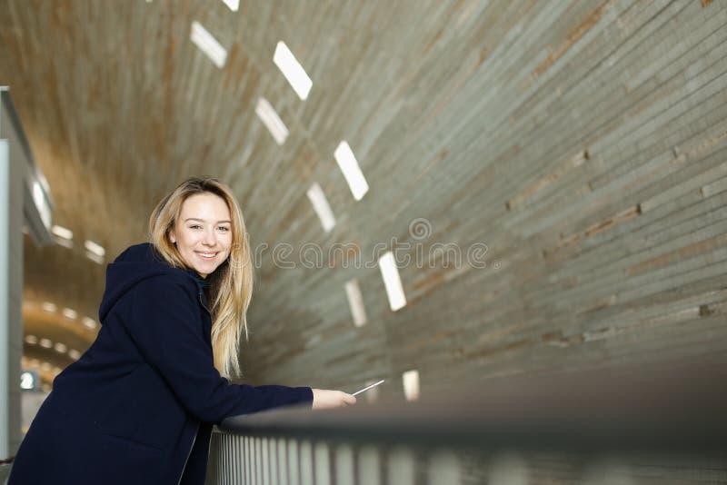 Personne féminine de sourire se tenant avec le smartphone moderne à l'arrière-plan lumineux monophonique photo stock
