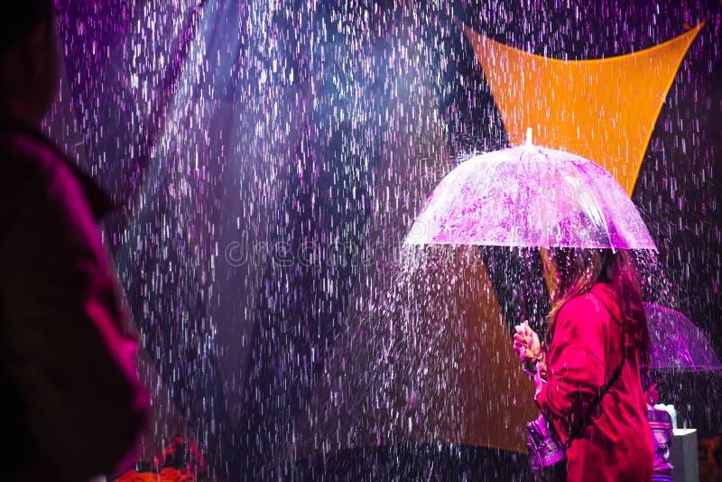 Personne féminine de vue arrière avec le parapluie sous la pluie artificielle venant du plafond et illuminée par les lumières col photographie stock
