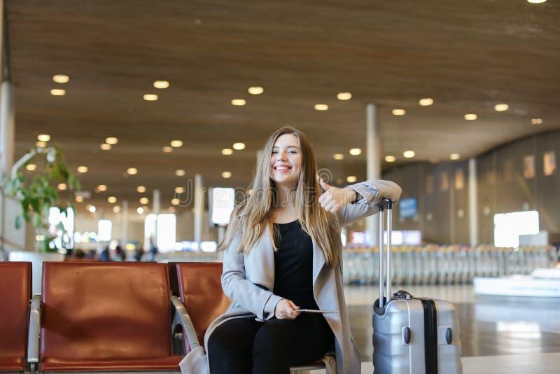 Personne féminine heureuse s'asseyant dans le hall d'aéroport avec le comprimé moderne près de la mallette et montrant des pouces photos stock