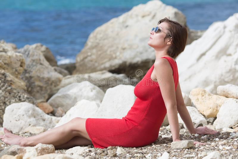 Personne féminine se reposant sur le bord de la mer rocheux image libre de droits