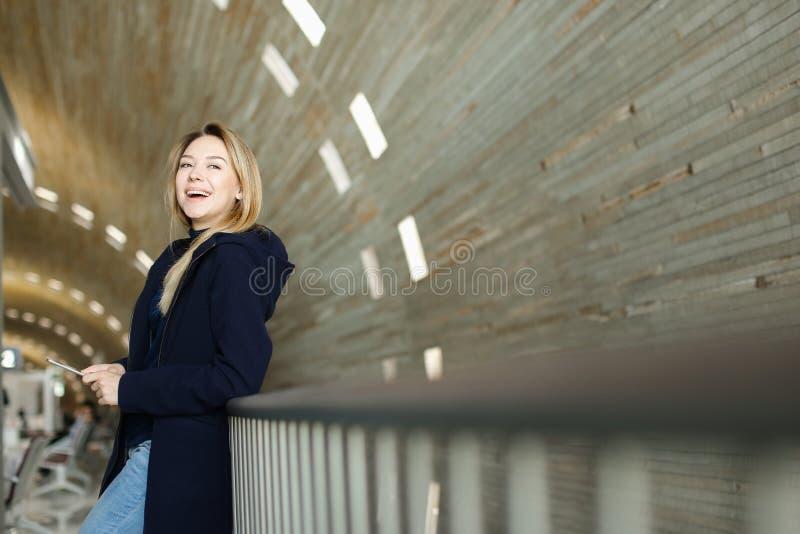 Personne féminine se tenant avec le smartphone moderne à l'arrière-plan lumineux monophonique photographie stock