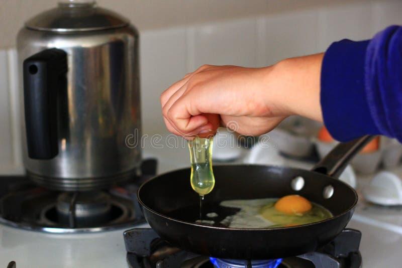 Personne faisant cuire des oeufs dans une casserole image stock