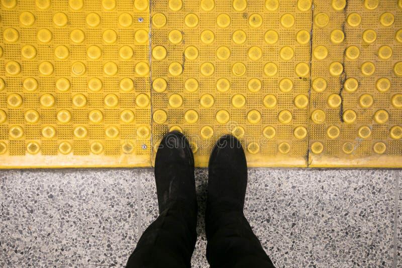 Personne faisant un pas sur la ligne jaune de sécurité photos stock