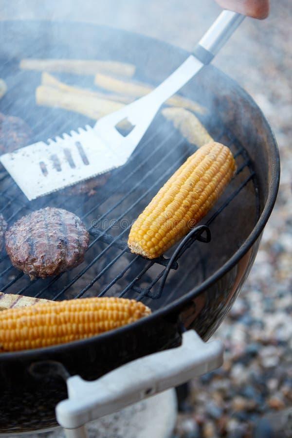 Personne grillant les hamburgers et le maïs sur un barbecue photos stock