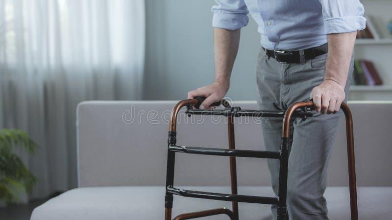 Personne handicapée essayant de se déplacer avec le cadre de marche à l'hôpital, réadaptation images stock