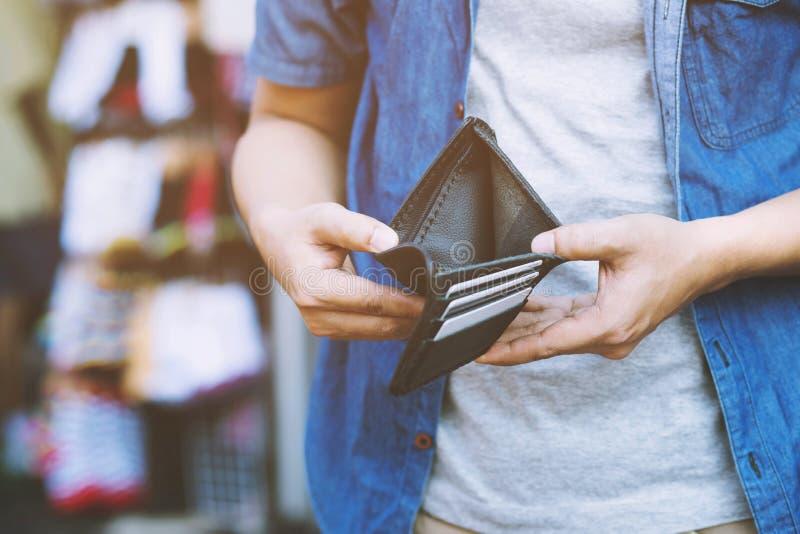 Personne haute étroite d'homme tenant un portefeuille vide dans les mains d'un homme aucun argent hors de la poche images stock