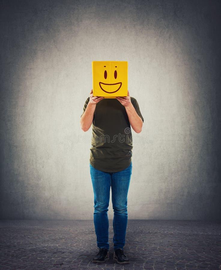 Personne incognito tenant une t?te jaune de bo?te ? la place Visage de dissimulation anonyme introverti derri?re le masque images stock