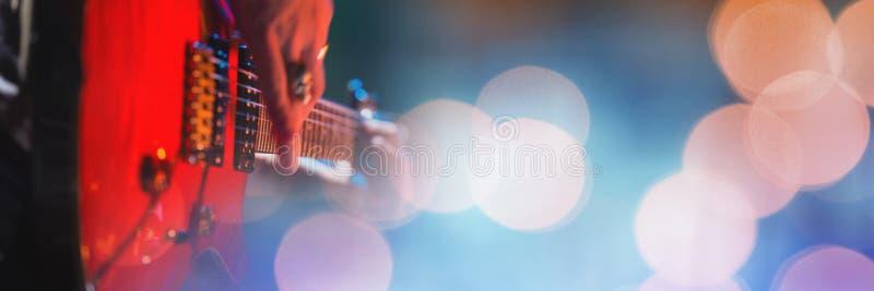 Personne jouant la guitare électrique avec les lumières jaunes photos stock