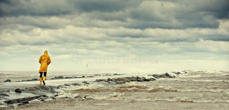 Personne marchant par la mer orageuse photo stock